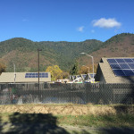 Roofs with solar panels in front of hills