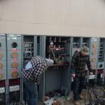 Workers wiring electric meter panels
